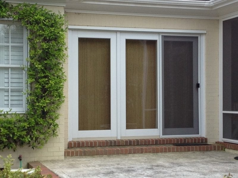 Closeup Accordion Shutters for Hurricane Protection between Ornamental Foliage on a House in Wilmington